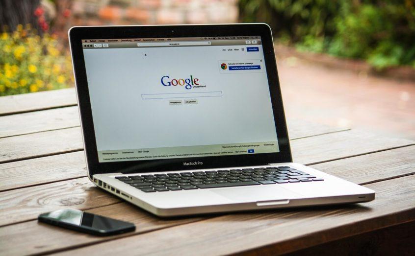 Ein Macbook und ein Handy liegen auf einem Tisch.