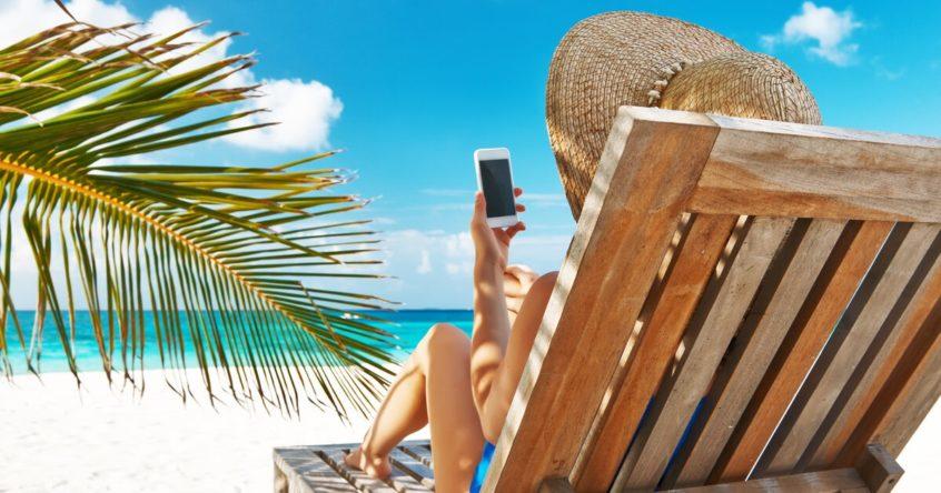 Eine Frau liegt mit ihrem Handy am Strand.