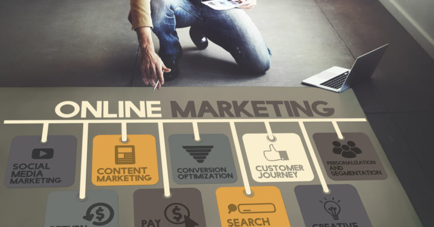 """Ein Mann kniet vor einem """"Online Marketing"""" Schriftzug"""