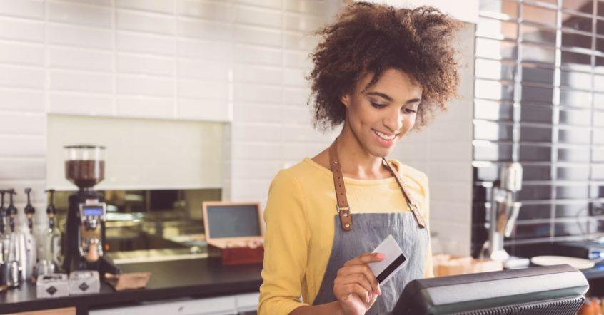Eine Frau scannt eine EC Karte an einer Kasse ein