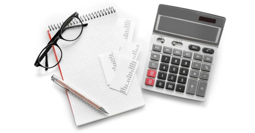 Ein Schreibblock auf dem ein Stift und eine Brille liegen, daneben ein Taschenrechner