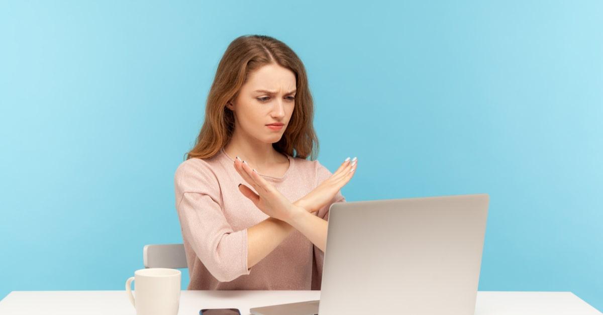 Eine Frau vor einem Notebook mit ablehnender Geste