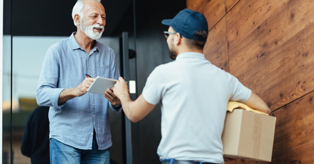 Ein älterer Herr nimmt ein Paket von seinem Postboten entgegen