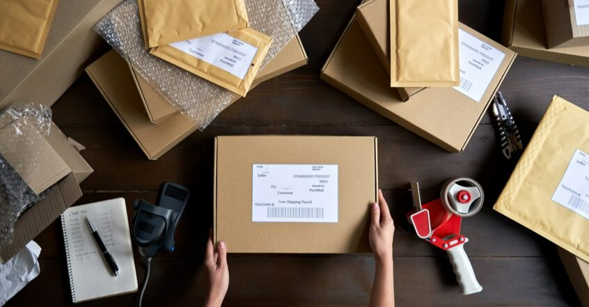 Vogelperspektive eines Tischens mit mehreren Paketen, 2 Hände verpacken ein Paket