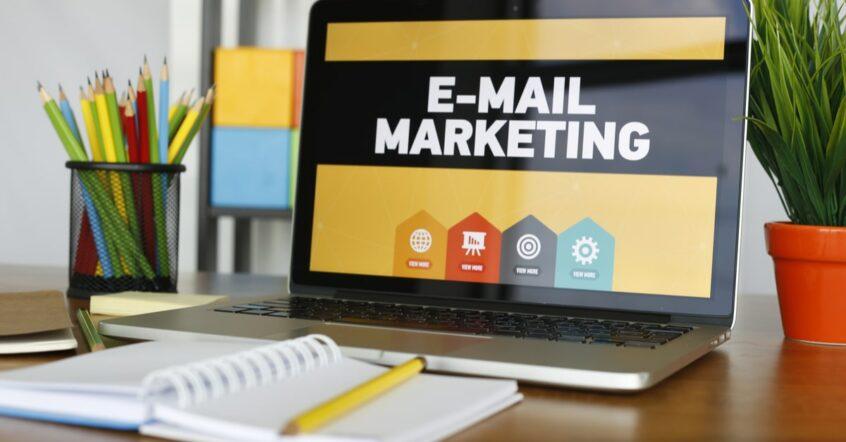 """Ein Notebook mit den Worten """"Email Marketing"""" auf dem Display, davor ein Notizblock mit Stift"""