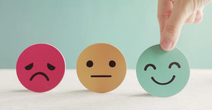 Drei aufgereihte Smileys: links roter, trauriger, mittig gelber mit neutralem Blick und rechts, von Daumen und Zeigefinger gehalten ein grüner, lächelnder.