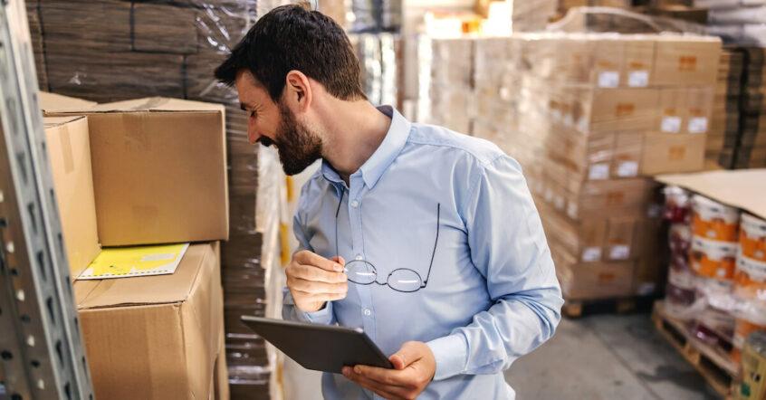 Attraktiver Mann mit Vollbart und Tablet in der Hand kontrolliert in einem Warenlager den Aufdruck auf einem Kartonstapel.